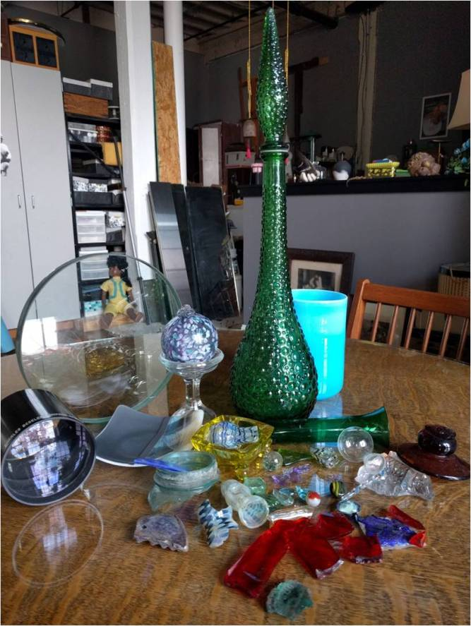 Assortment of art glass and broken bits of colorful glass on table top
