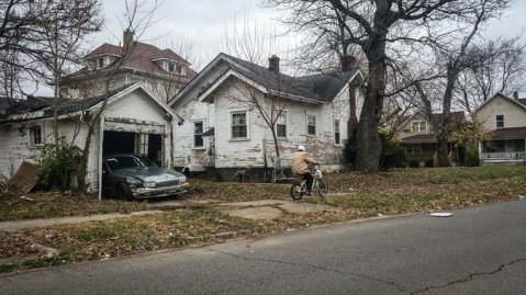 Raggedy old house with abandoned car in falling down garage